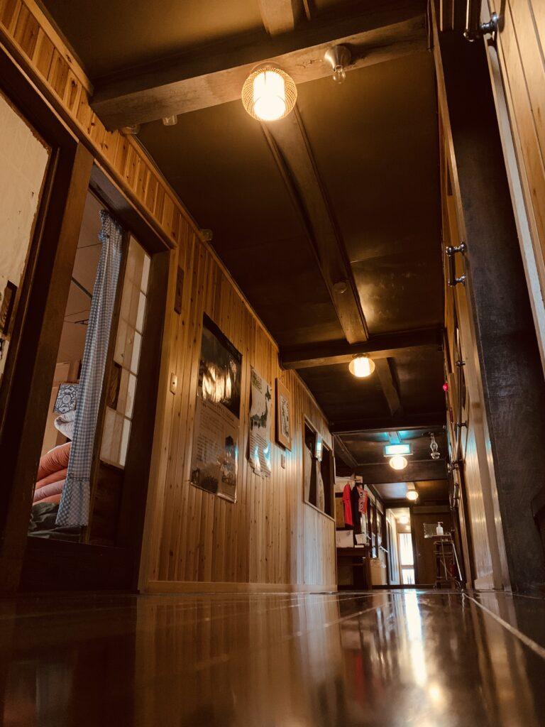 木造の暖色が優しく光る温泉旅館の廊下