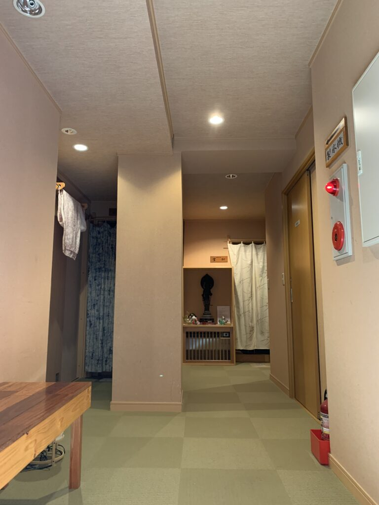 浴場入口の暖簾が見えるカーペット敷きの廊下